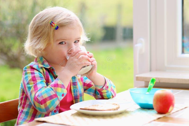 Menina bonito que come o brinde e o leite para o café da manhã fotografia de stock royalty free