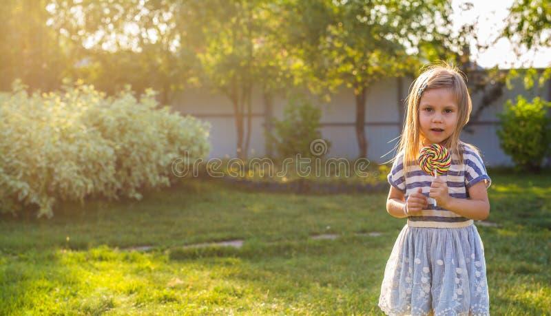 Menina bonito que come um pirulito na grama no verão foto de stock royalty free