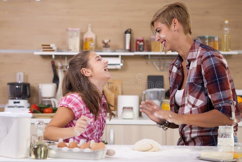 Menina bonito que cozinha com seu alimento saudável da mãe fotografia de stock royalty free