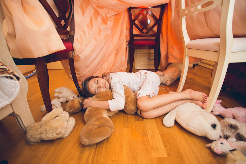 Menina bonito que dorme no assoalho com os brinquedos no quarto imagens de stock