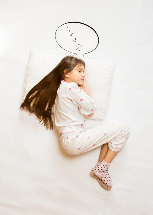 Menina bonito que dorme no coxim grande com bolha do discurso fotografia de stock