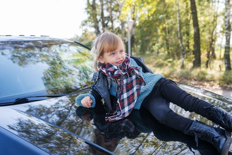 Menina bonito que encontra-se no telhado do carro fora fotografia de stock royalty free