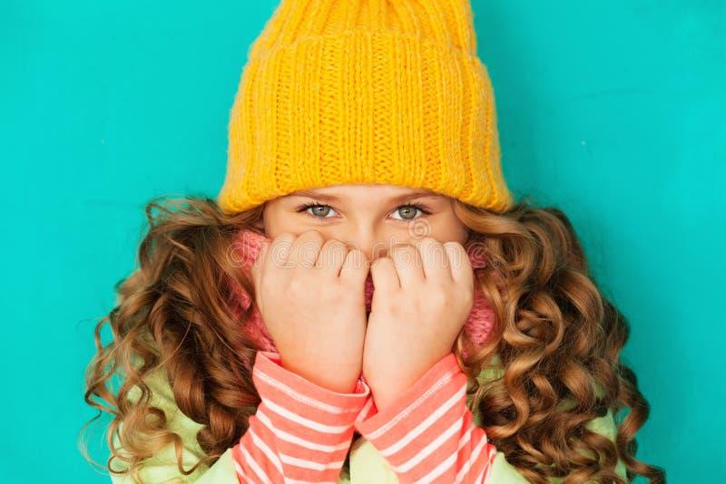 Menina bonito que esconde atrás de seu lenço imagem de stock