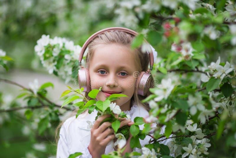 Menina bonito que escuta a m?sica em uma ?rvore da flor da ma?? louro ador?vel que aprecia a m?sica nos fones de ouvido fora em u fotos de stock