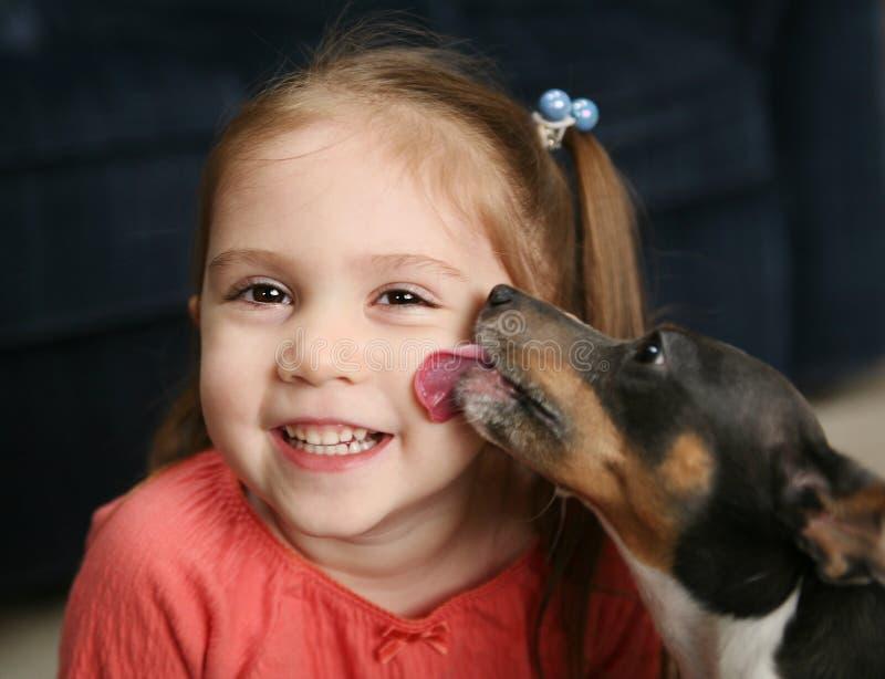 Menina bonito que está sendo lambida por um cão imagem de stock