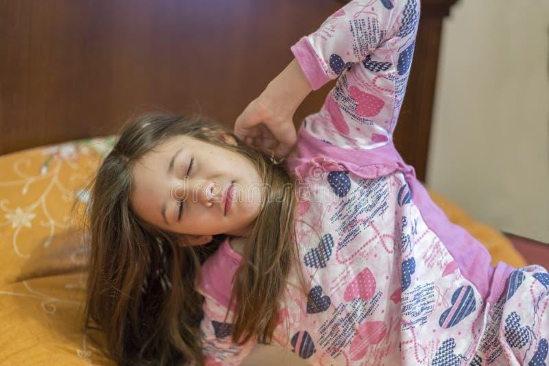 Menina bonito que estica seus braços felizmente com um sorriso de acordar em sua cama Bocejo sonolento da criança na cama Pequeno fotos de stock