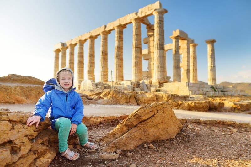 Menina bonito que explora o templo do grego clássico de Poseidon no cabo Sounion, um dos monumentos principais da época dourada d foto de stock