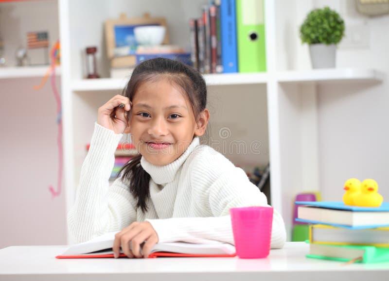 A menina bonito que faz os trabalhos de casa que leem uma coloração do livro pagina o wr fotografia de stock royalty free