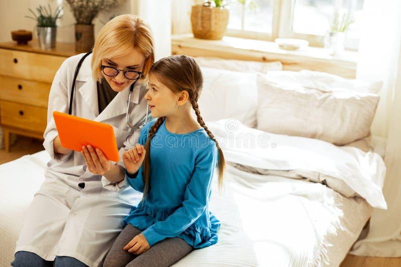 Menina bonito que faz perguntas quando um doutor que olha a tabuleta imagem de stock