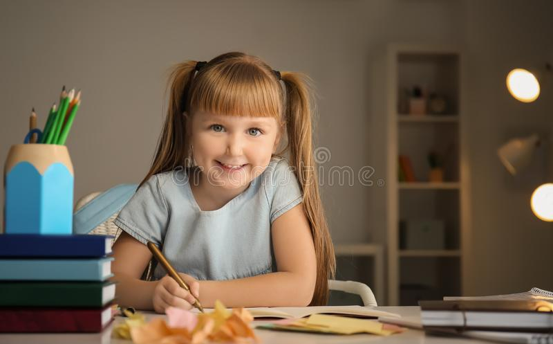 Menina bonito que faz suas lições em casa fotografia de stock