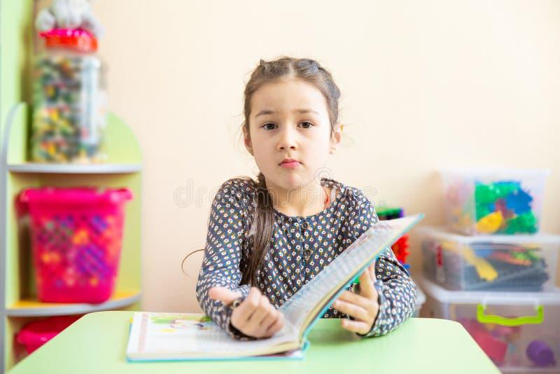Menina bonito que faz trabalhos de casa, lendo um livro, umas páginas colorindo, uma escrita e uma pintura Pintura das crianças T fotografia de stock royalty free