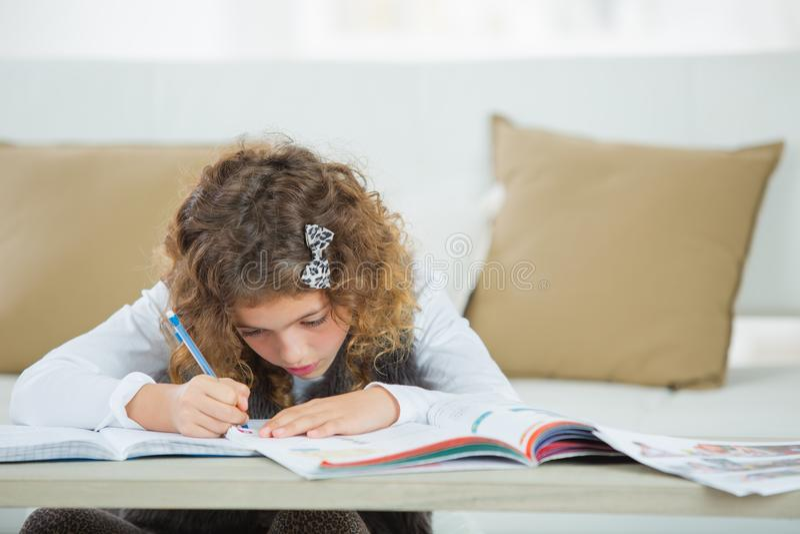Menina bonito que faz trabalhos de casa para a escola fotografia de stock