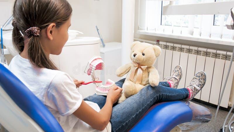 A menina bonito que finge como seu urso de peluche é paciente no escritório do dentista foto de stock
