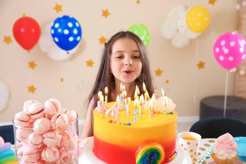 Menina bonito que funde para fora velas em seu bolo de aniversário fotografia de stock royalty free