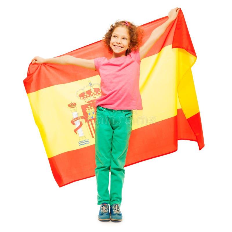 Menina bonito que guarda a bandeira espanhola atrás dela imagens de stock royalty free