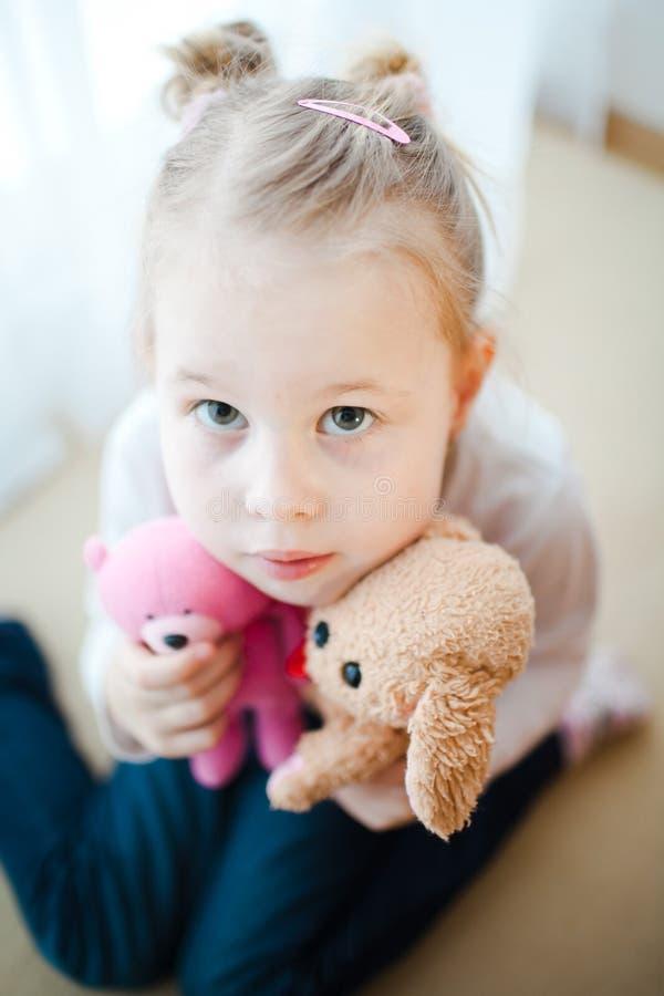 Menina bonito que guarda dois ursos de peluche - focalizados rasamente em seus olhos imagens de stock royalty free