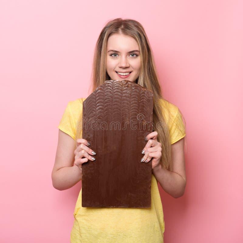 Menina bonito que guarda e que come a barra de chocolate gigante do cacau perto da parede cor-de-rosa imagem de stock royalty free