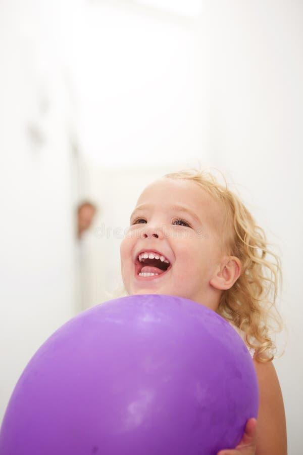 Menina bonito que guarda o balão e o riso foto de stock royalty free