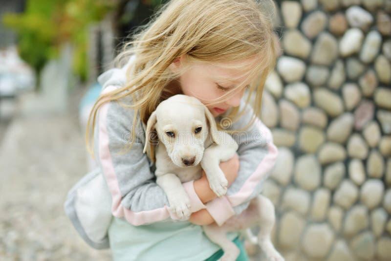Menina bonito que guarda o cachorrinho branco pequeno fora Criança que joga com o cão do bebê no dia de verão fotos de stock