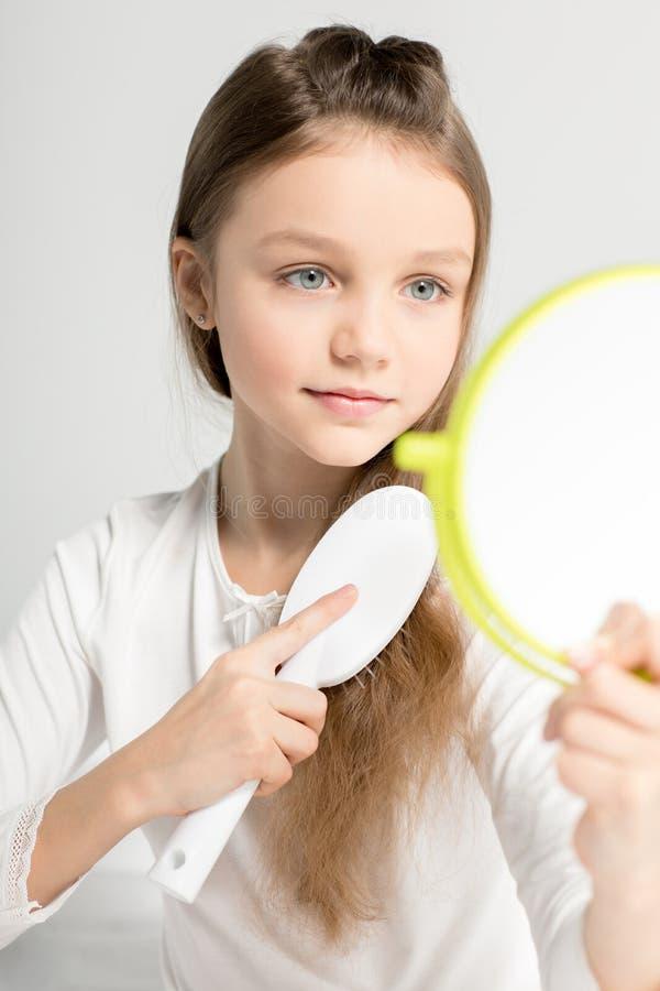 Menina bonito que guarda o espelho de mão e que penteia o cabelo fotos de stock