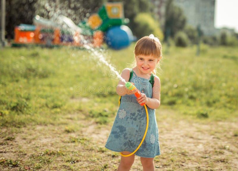 Menina bonito que joga a arma de água fotografia de stock royalty free