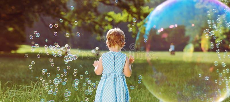 Menina bonito que joga as bolhas de sabão imagem de stock