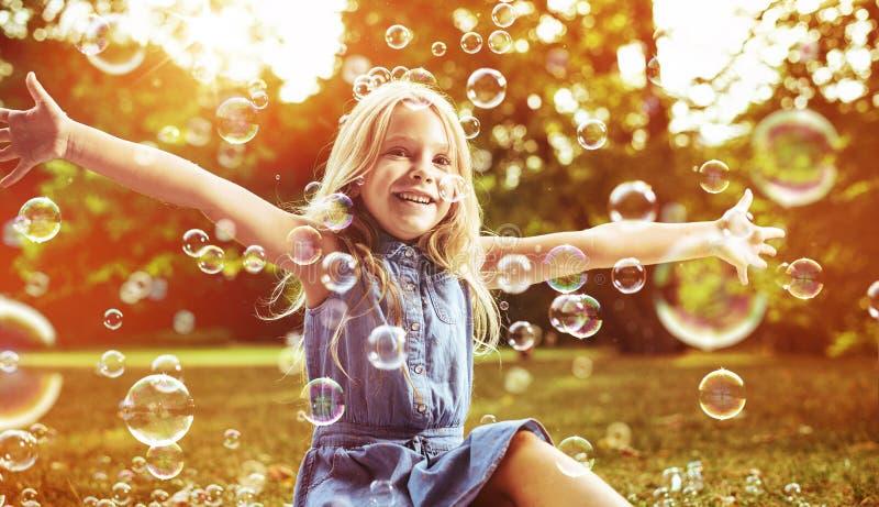 Menina bonito que joga bolhas de sabão fotografia de stock royalty free