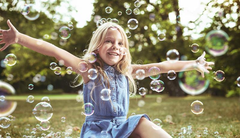 Menina bonito que joga bolhas de sabão imagem de stock