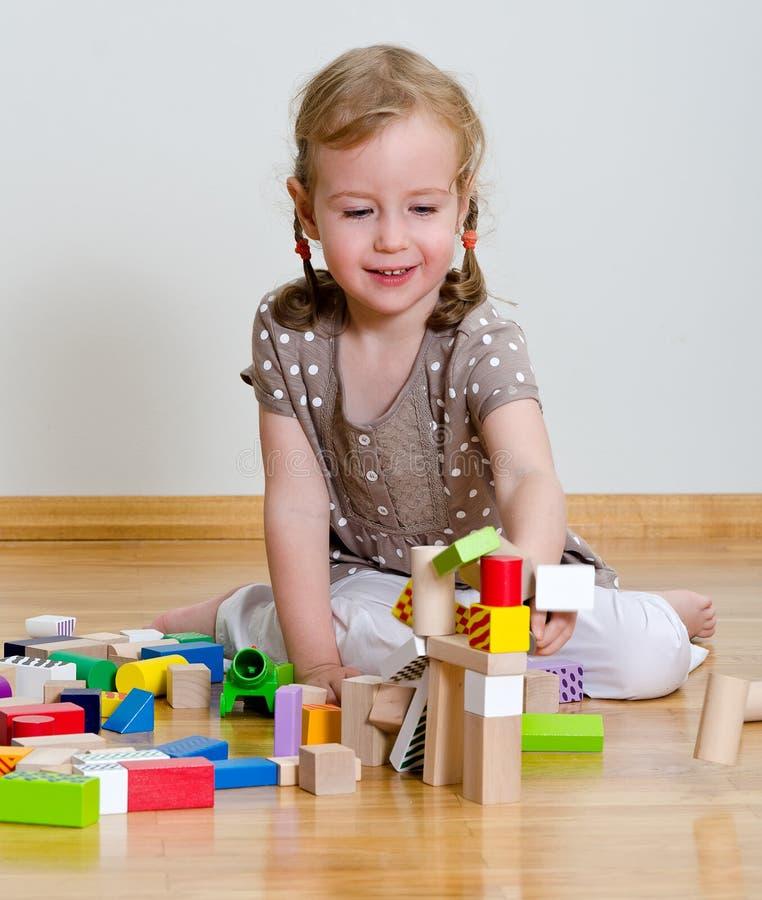 Menina bonito que joga com blocos de apartamentos fotografia de stock royalty free