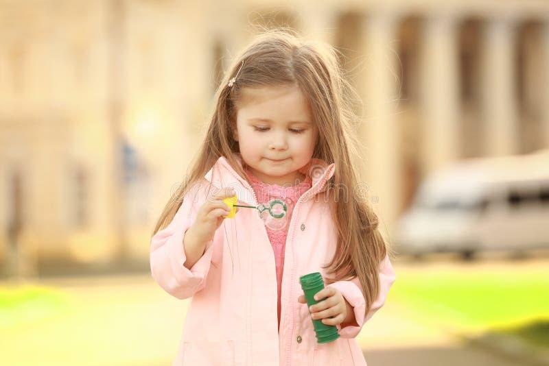 Menina bonito que joga com bolhas de sabão fora fotos de stock royalty free