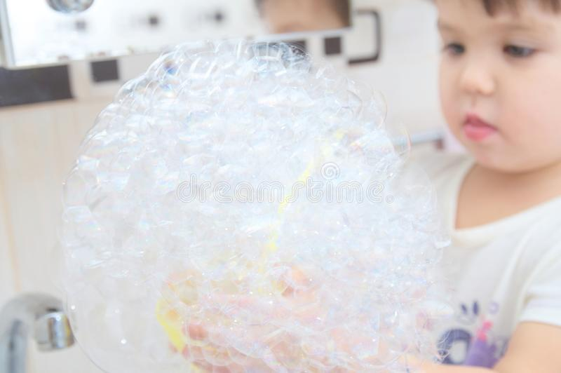 Menina bonito que joga com bolhas de sabão no banheiro foto de stock royalty free