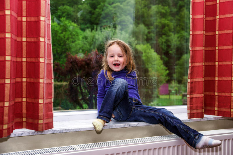 A menina bonito que joga com drapeja na janela imagens de stock