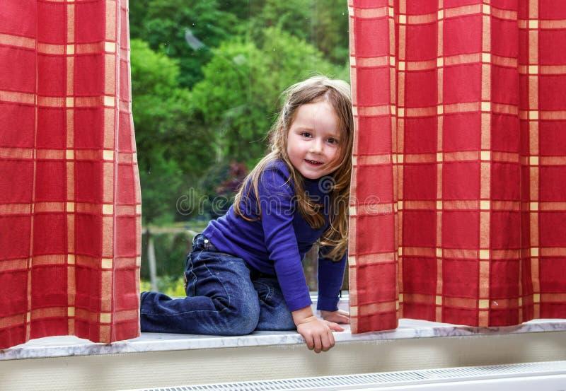 A menina bonito que joga com drapeja na janela imagem de stock royalty free
