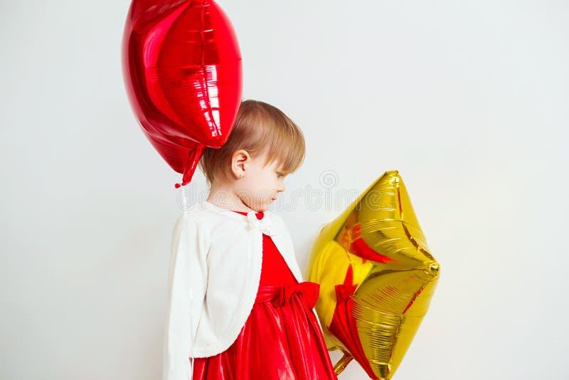 A menina bonito que joga com estrela deu forma a balões na frente de w fotografia de stock royalty free