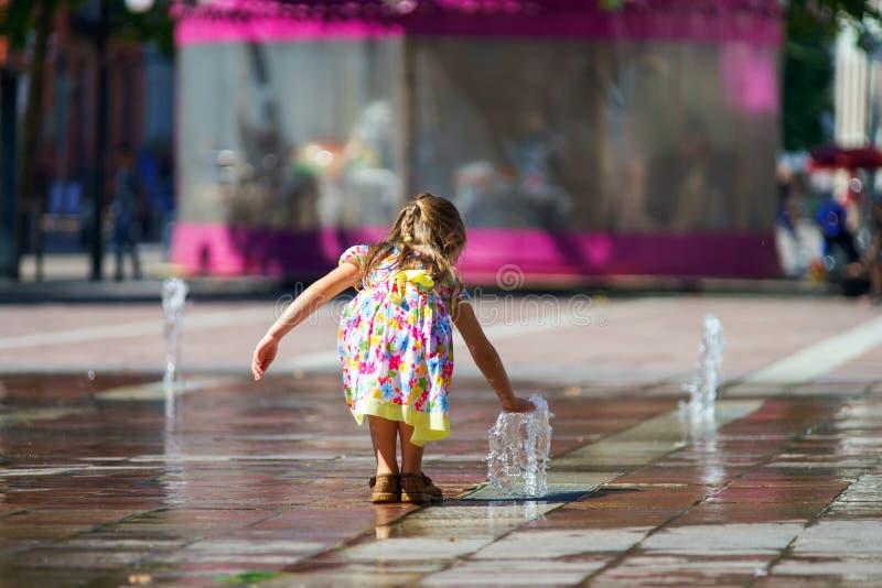 Menina bonito que joga com respingo da fonte fotografia de stock royalty free