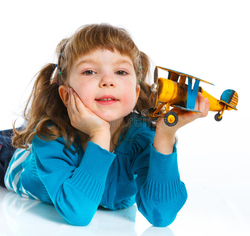 Menina bonito que joga com um avião do brinquedo imagens de stock royalty free