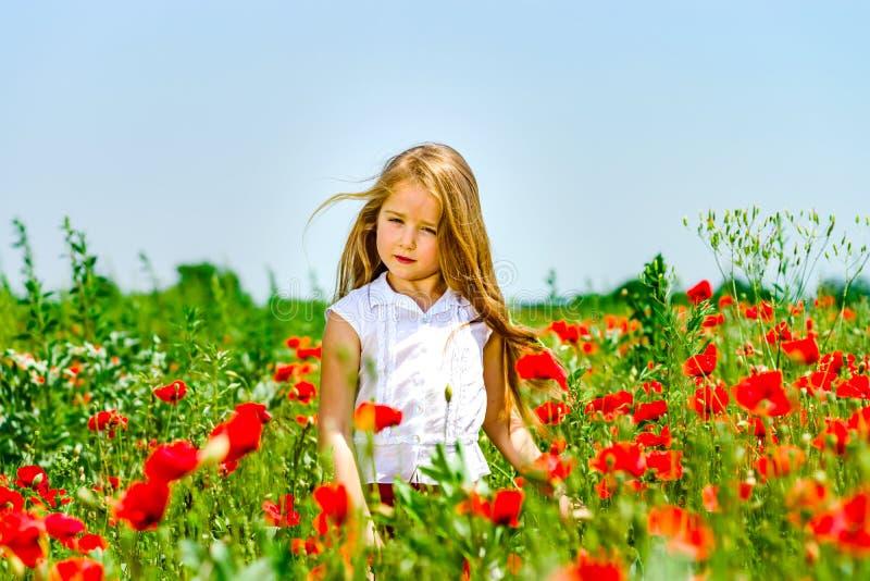 A menina bonito que joga em papoilas vermelhas coloca o dia de verão, beleza imagens de stock