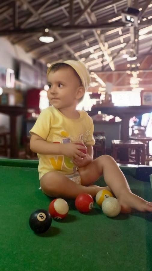 Menina bonito que joga na mesa de bilhar com bolas fotografia de stock