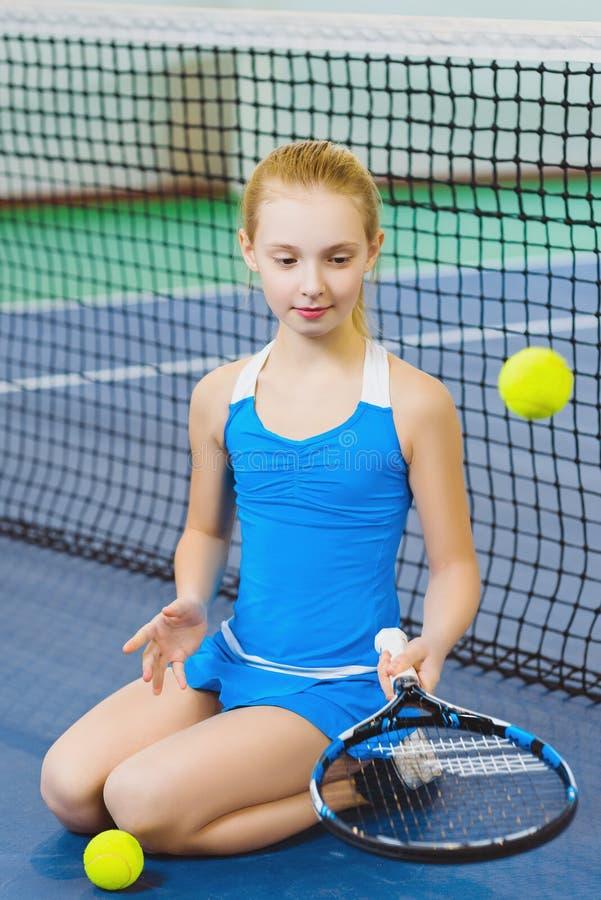 Menina bonito que joga o tênis e que levanta no tribunal interno imagem de stock royalty free