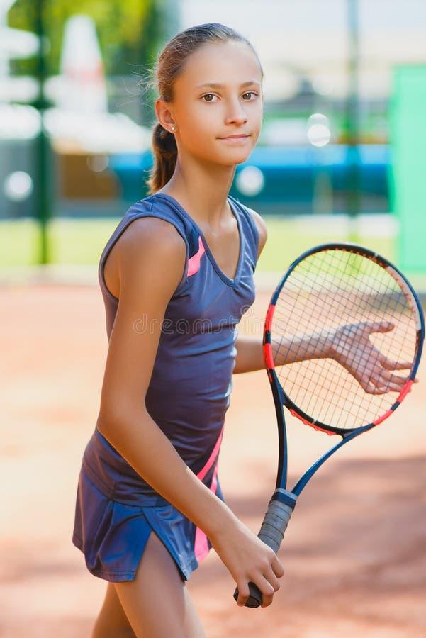 Menina bonito que joga o tênis e que levanta no tribunal interno fotografia de stock royalty free