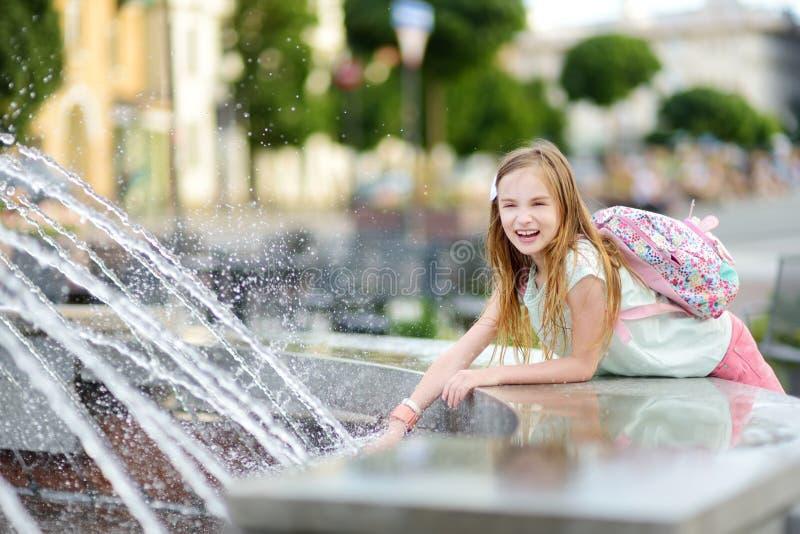Menina bonito que joga pela fonte da cidade no dia de verão quente e ensolarado Criança que tem o divertimento com água no verão fotos de stock royalty free