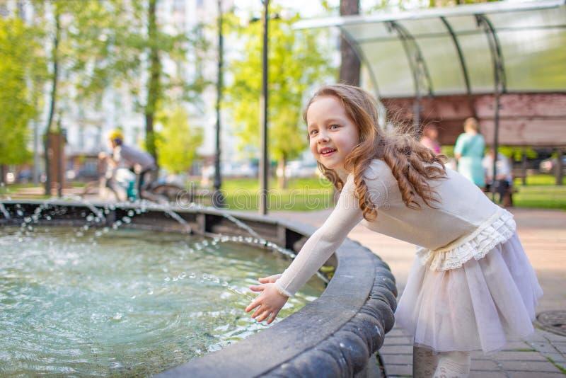 Menina bonito que joga pela fonte da cidade no dia de verão quente e ensolarado Criança que tem o divertimento com água no verão  imagens de stock royalty free