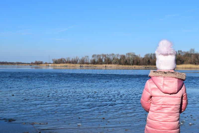 Menina bonito que joga perto do lago no parque do outono fotografia de stock