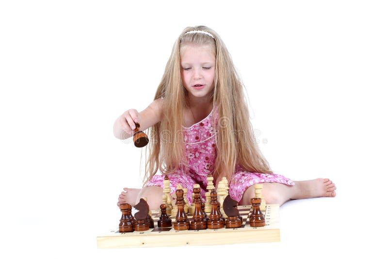 Menina bonito que joga a xadrez foto de stock royalty free