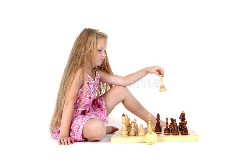 Menina bonito que joga a xadrez imagem de stock royalty free