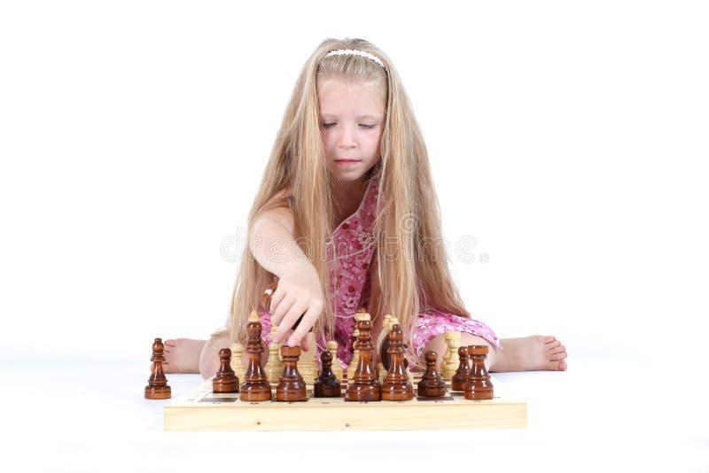Menina bonito que joga a xadrez no branco fotografia de stock