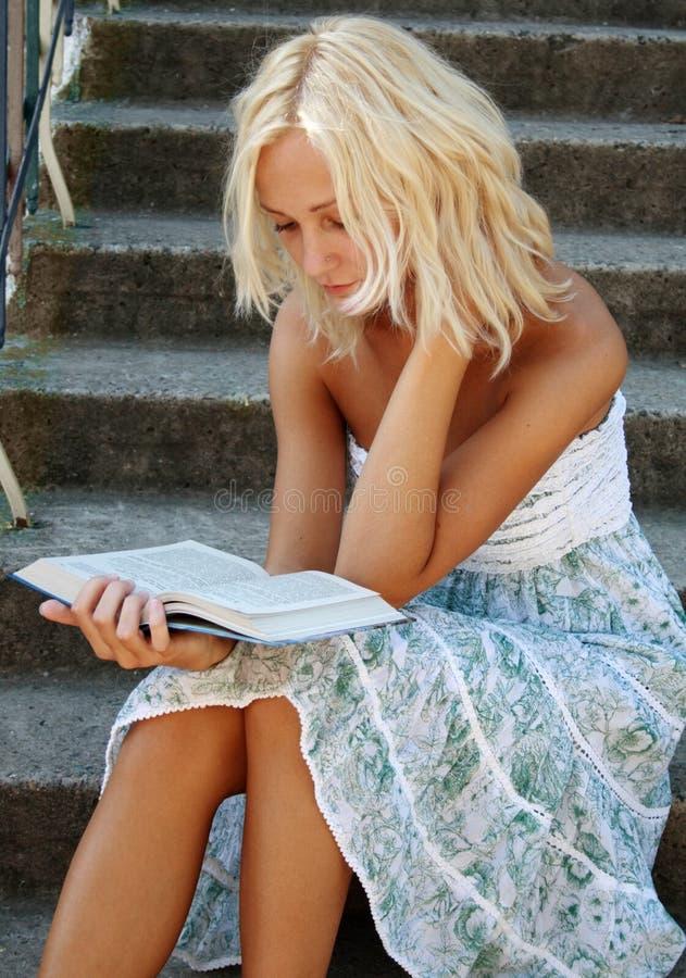 Menina bonito que lê um livro imagem de stock