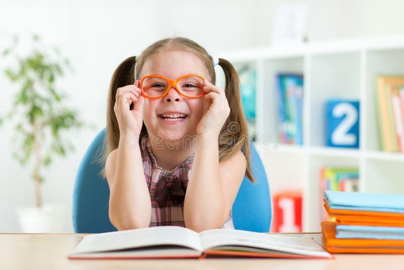 Menina bonito que lê um livro ao vestir fotografia de stock
