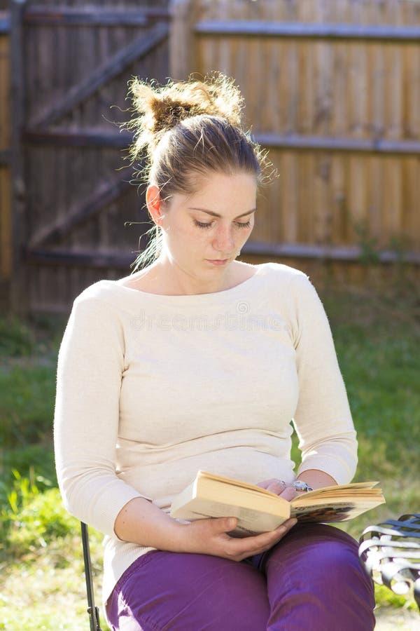 Menina bonito que lê um livro exterior fotografia de stock royalty free
