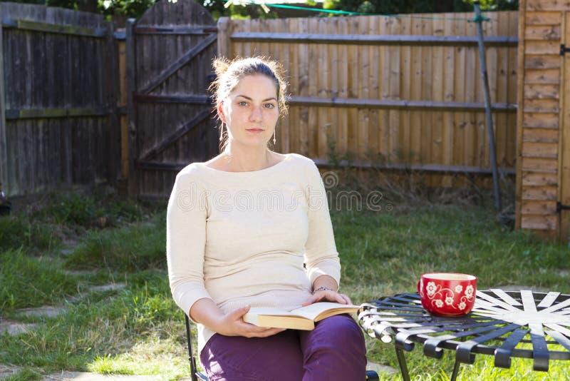 Menina bonito que lê um livro exterior foto de stock